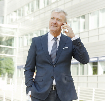 Businessman making call while standing in front of a building