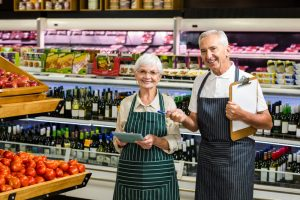 Smiling senior workers with clipboard in supermarket