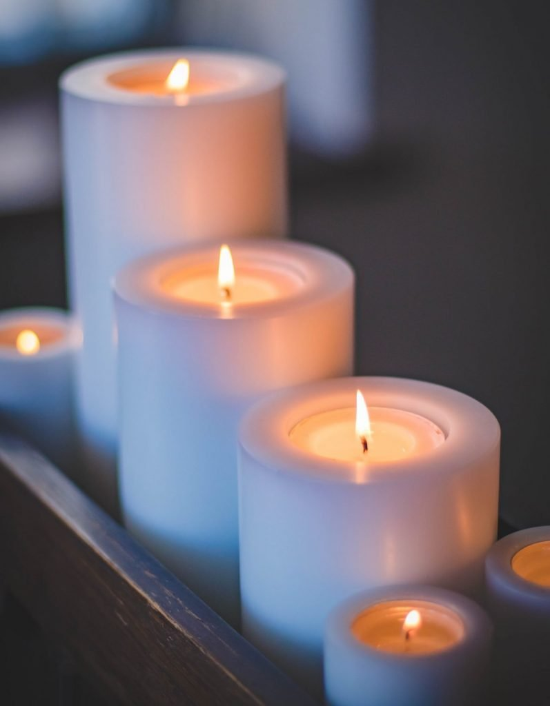 Candles provide less light than light bulbs and much less blue light which keeps you awake.