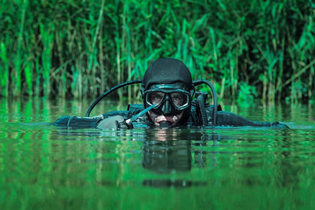 Picture of a navy seal who subscribes to hormetic training, diving in a jungle