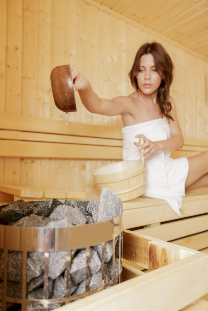 Woman controlling the right dose of heat to improve her health from heat of sauna