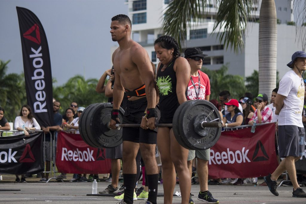 weightlifting couple demonstrating their skills outside