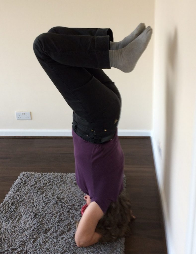 Illustrating on how standing on your head is great exercise indoors