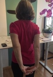 Author squeezing shoulder blades together with interlaced hands behind back