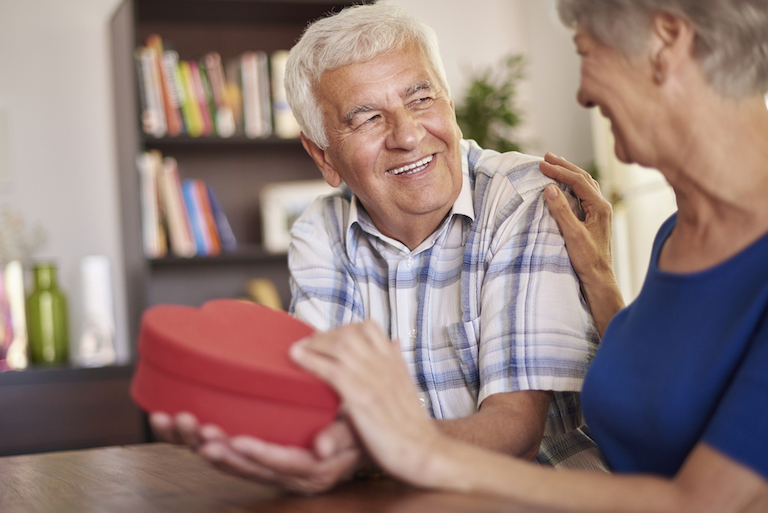 Happy husband giving romantic chocolate box gift to delighted wife