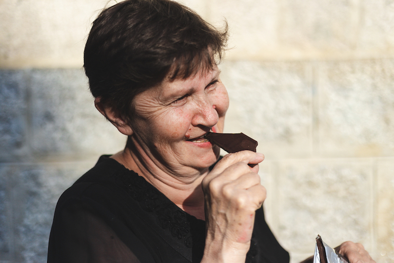 Older lady smiling as she eats dark chocolate